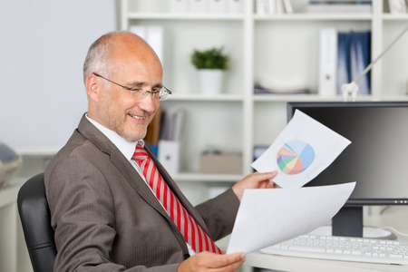 Side view of mature businessman analyzing documents at office desk photo