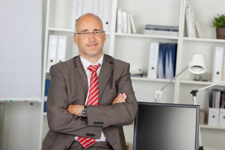 successful businessman with folded arms leaning on desk photo