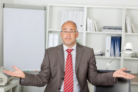 Portrait of mature businessman shrugging shoulders in office photo