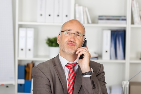 puckering lips: Mature businessman puckering lips while using cordless phone in office