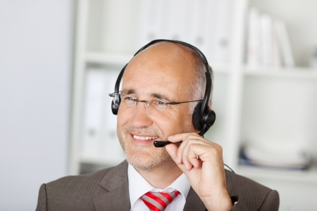 Closeup of mature customer service operator using headset in office photo