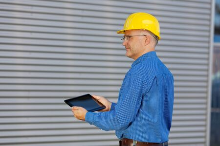 btp: Side view of thoughtful mature architect using digital tablet