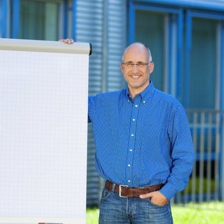 Portrait of confident businessman with hand in pocket standing by flipchart photo