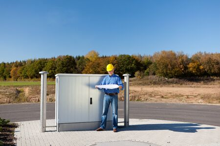 Full length of mature architect holding blueprint while standing against electric box photo