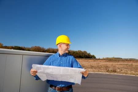 Male architect examining blueprint while standing against clear sky photo