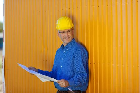 Mature male architect wearing hardhat with blue print against trailer photo