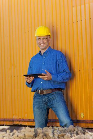 Portrait of confident male architect holding digital tablet against trailer photo