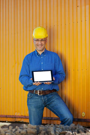 man front view: Portrait of confident male architect showing digital tablet against trailer
