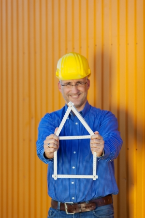 Portrait of mature male architect holding house frame while standing against trailer photo