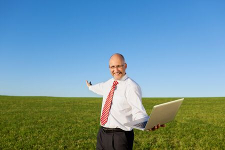 filed: Portrait of excited mature businessman with arms outstretched holding laptop on filed against clear sky