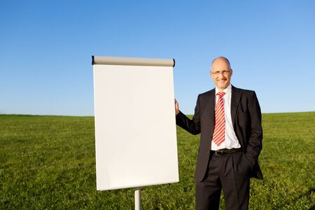 Portrait of mature businessman with hand in pocket standing by blank flipchart on grassy field against clear sky photo