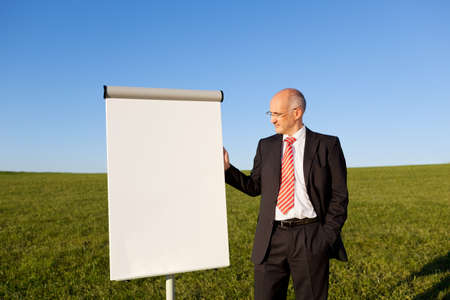 Portrait of mature businessman standing by blank flipchart on grassy field against clear sky photo