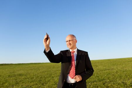 Mature businessman writing on invisible screen with marker on field against clear sky photo