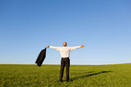 outstretched arms: Full length rear view of businessman with arms outstretched standing on grassy field against clear sky Stock Photo