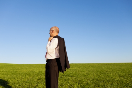 Side view of thinking businessman standing on grassy field against clear sky photo