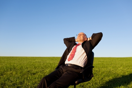 Mature businessman sitting on chair in grassy field against clear sky photo