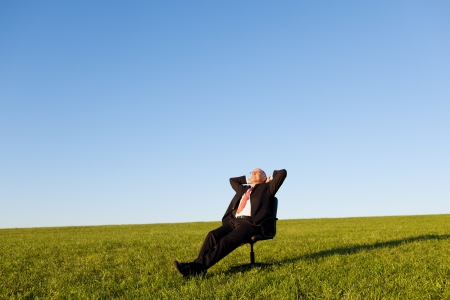 Relaxed businessman sitting on green grassland under blue sky photo