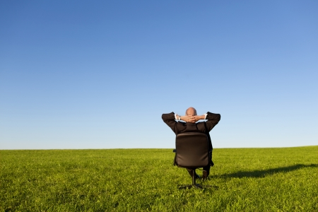 Businessman sitting on green grassland under blue sky photo