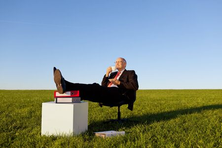 Full length of relaxed businessman enjoying coffee on chair in grassy field against clear sky photo