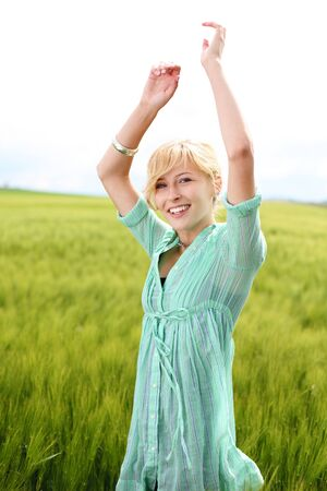Beautiful woman enjoying the outdoors and nature standing in a field of long green grass with her arms raised Reklamní fotografie