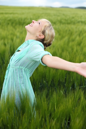 Beautiful woman rejoicing in the summer standing in long fresh green grass in the countryside with her arms outstretched and head tilted to the sun photo