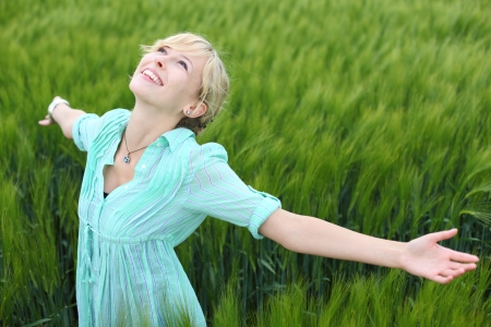 arm extended: Pretty woman rejoicing in a green field standing with her arms spread wide open enjoying the beauty and tranquillity of nature Stock Photo