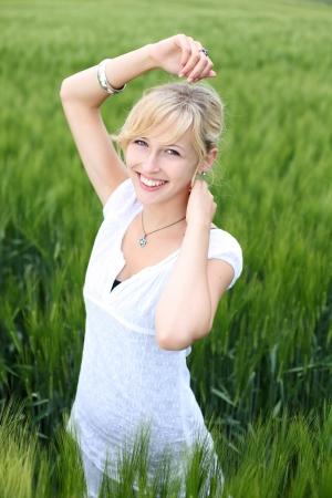 Smiling blond female enjoying the fresh air in cornfield Stock Photo - 21195278