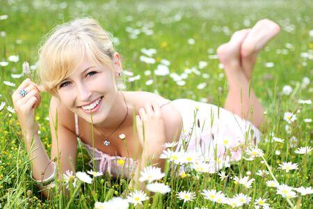 pieds nus femme: Belle jeune femme aux pieds nus dans une robe d'�t� reposantes parmi les marguerites blanches dans un pr� herbeux