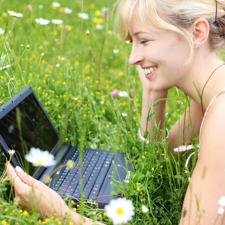 netbook: Happy woman using her notebook outdoors lying in a field of fresh white spring daisies smiling at information on the laptop screen