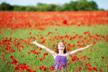 arm extended: Laughing young girl in a poppy field surrounded by red flowers looking up into the sunshine with her arms outstretched