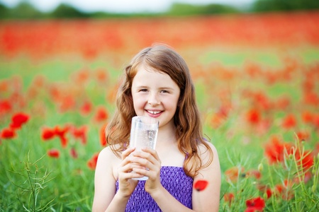 Smiling girl with a large glass of cold sparkling mineral water clasped in her hands a she quenches her thirst in a colourful red poppy field photo