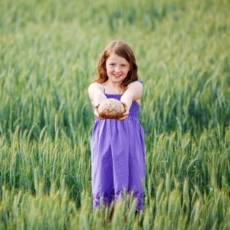 Beautiful child showing bread over the cornfield landscape photo