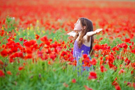 stretched out: Cheerful young child enjoying the fresh air in flower field