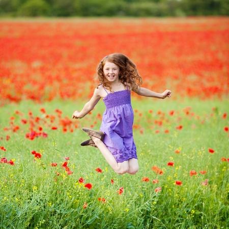 glädje: Glada ung kvinna hoppar på en ny blomma fält