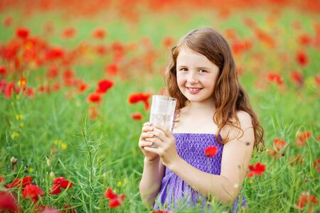 Caucasian young female holding a glass of water in a flower field photo