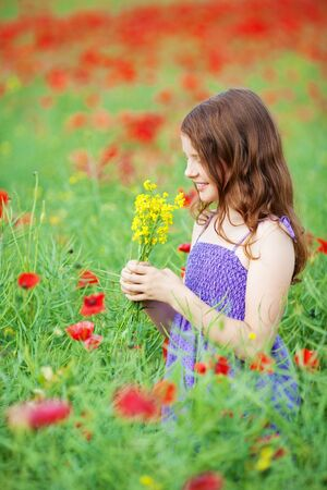 contented: Side view shot of smiling beautiful girl smelling a bunch of flower