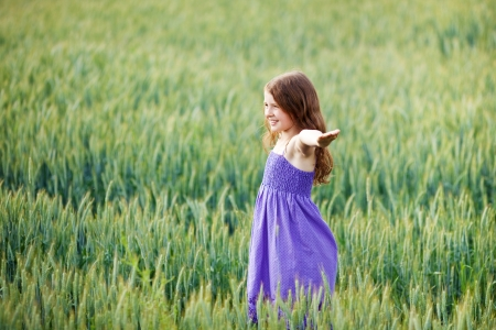 outspread: Young girl playing in a wheatfield dancing around with her arms outspread with a beautiful smile on her face