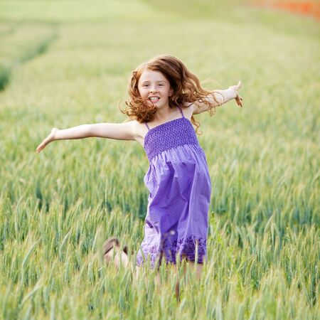 outstretched arms: Happy carefree young teenage girl in a cornfield jumping for joy with her arms outstretched as she enjoys the summer
