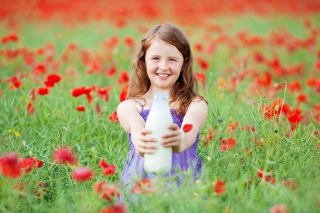 Smiling young girl showing a bottle of milk in flower field photo