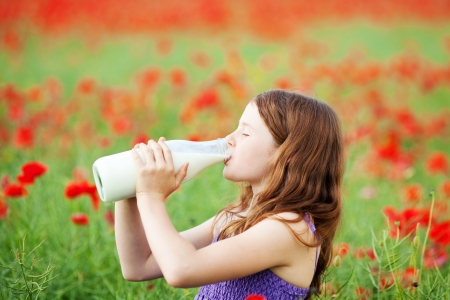 Young girl enjoying a drink of milk from a glass bottle standing in field of red poppies photo