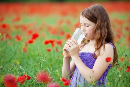 Portrait of little girl drinking a glass of water in flower field photo