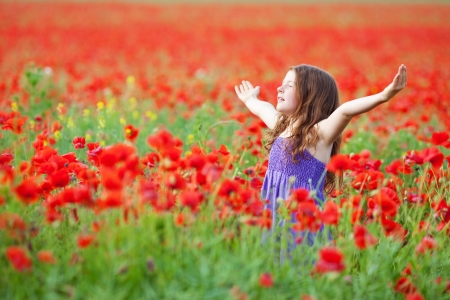 bliss: Beautiful young girl feel the fresh air in flower field