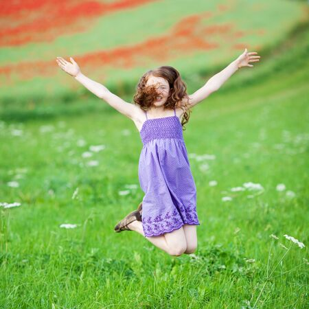 outspread: Young girl jumping for joy in a lush green meadow with her arms outspread and hair flying about her face