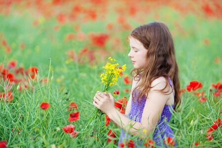 Pretty little girl smelling a bunch of yellow flowers that she is holding in her hands while standing in a field of poppies photo