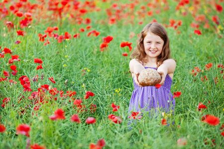 Smiling girl holding a wheat bread in beautiful flower field photo