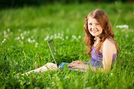 Smiling pretty little girl sitting on the grass field while browsing the internet photo