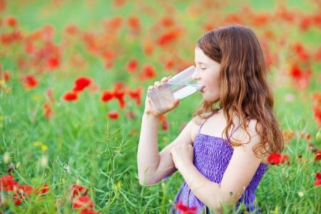 tomando agua: Muchacha caucásica joven beber un vaso de agua en el campo Foto de archivo