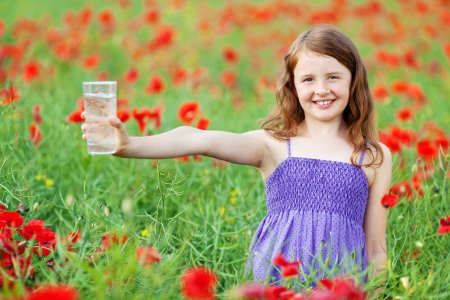 field glass: Smiling little child holding a glass of water in flower field