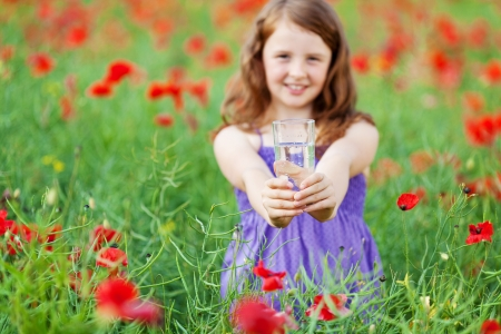 Beautiful Caucasian girl giving a glass of water over the Greenfield photo
