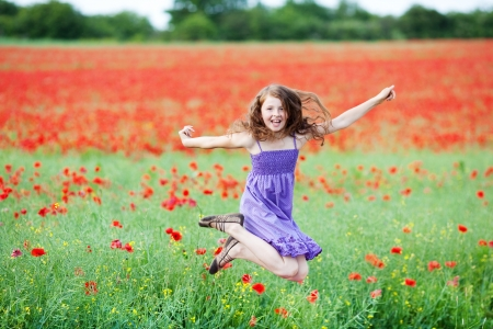 Young girl jumping for joy in a field of red poppies as she celebrates the summer vacation Stock Photo
